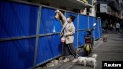 一名武漢婦女把一個食品袋遞給在路障後的人。(2020年4月1日)