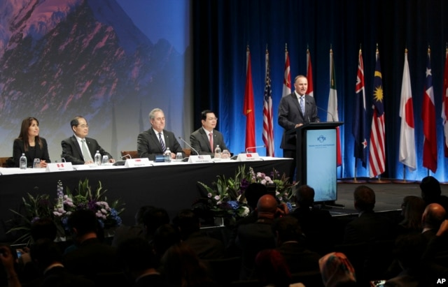 New Zealand Prime Minister John Key, right, speaks to delegates at the signing of the Trans-Pacific Partnership agreement in Auckland, New Zealand, Feb. 4, 2016.