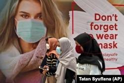 Sejumlah perempuan bermasker melewati iklan yang mempromosikan kesadaran akan wabah virus corona di sebuah pusat perbelanjaan di Jakarta, Rabu, 1 Juli 2020. (Foto: AP/Tatan Syuflana)