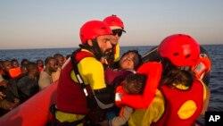 Une Nigériane et son bébé sont secourus en mer Méditerranée par des membres de l'ONG Proactiva Open Arms au large de Sabratah, Libye, 20 août 2016.