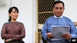 Burma's Labor and Social Welfare Minister Aung Kyi, right, reads a statement to the media after meeting with Aung San Suu Kyi, left, at Seinlekhanthar government guest house in Yangon, July 25, 2011