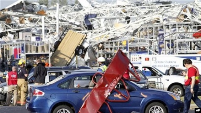 Emergency personnel work around a Lowes Home Improvement store after it was hit by a tornado in Sanford, North Carolina, April 16, 2011