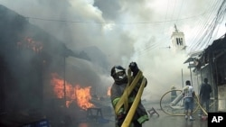 A firefighter untangles a hose during a blaze at the a street market in Tegucigalpa, Honduras, Saturday Feb. 18, 2012.