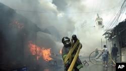 A firefighter untangles a hose during a blaze at the a street market in Tegucigalpa, Honduras, Saturday Feb. 18, 2012.