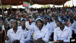 Women wave South Sudanese flags as they attend the country's anniversary celebrations, at the John Garang mausoleum in Juba, South Sudan, Monday, July 9, 2012.