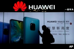 FILE - A woman browses her smartphone as she walks by a Huawei store at a shopping mall in Beijing, Dec. 11, 2018.