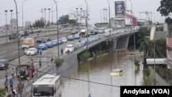 Sebuah bis dan taksi (kuning) tenggelam hingga setengah badan kendaraan di kawasan Grogol, Jakarta, 10 Februari 2015. (Foto: VOA/Andylala)