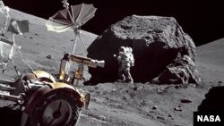 Astronaut Harrison Schmitt examines a huge rock on the moon. The Lunar Roving Vehicle is in the foreground.