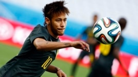 Brazil's Neymar eyes the ball during his team's final practice in Sao Paulo one day before the opening match of the soccer World Cup between Brazil and Croatia, June 11, 2014.