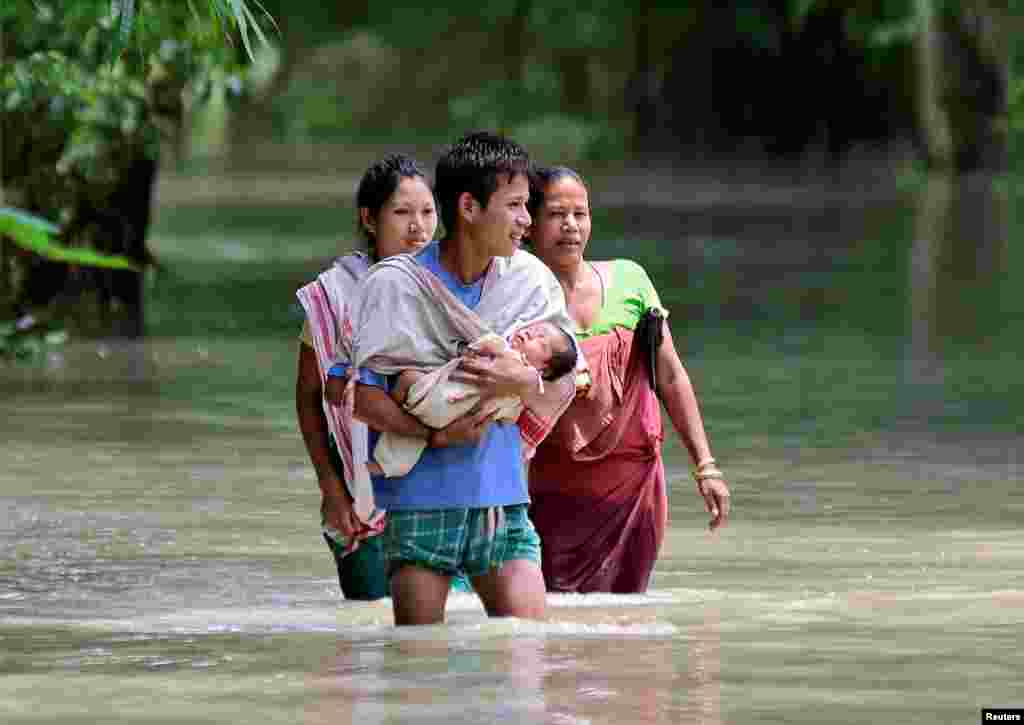 A man carries his new born baby as he and his family members wade through a flooded area to reach a relief camp at a village in Barpeta district of the northeastern state of Assam, India.