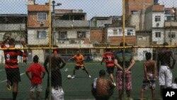 Warga bermain sepak bola di Nova Holanda, kawasan kumuh di Mare, Rio de Janeiro, Brazil, Minggu 30 Maret 2014.
