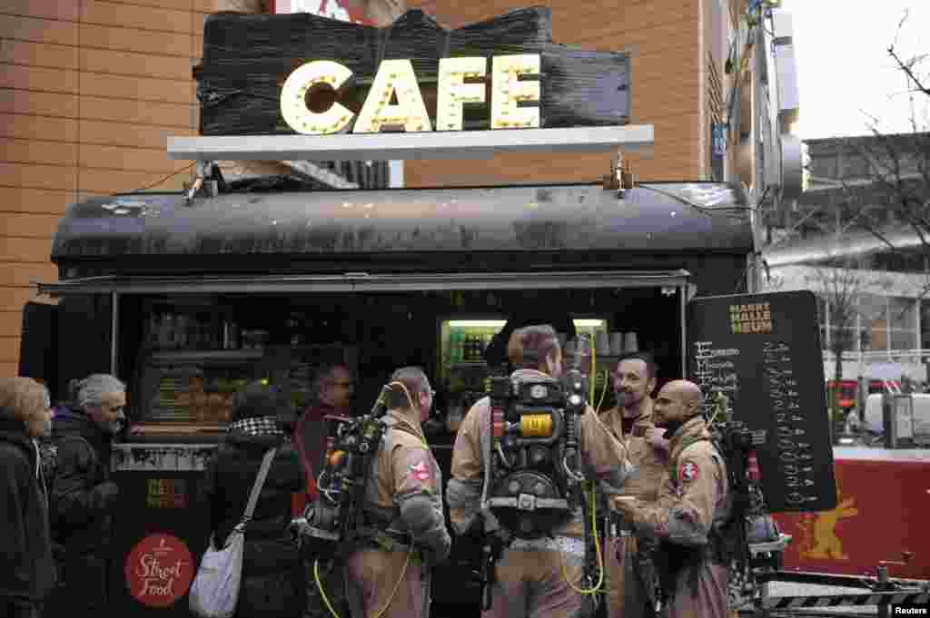 Members of a German Ghostbusters fanclub dressed as the film's characters, drink coffee at a street food market at the 66th Berlinale International Film Festival in Berlin, Germany.