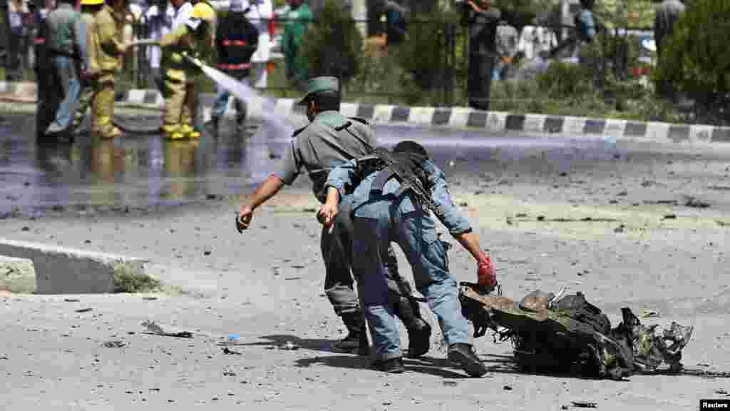 Afghan policemen drag a piece of debris from a vehicle used in a suicide car bomb attack, in Kabul, Aug. 10, 2014.