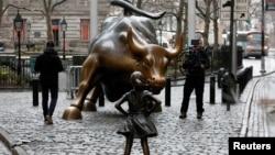 """紐約著名的""""華爾街銅牛""""與對面的""""無畏女孩""""塑像。"""