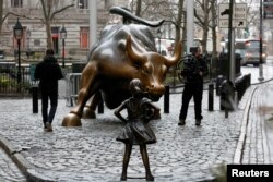 FILE - A statue titled Fearless Girl faces the Wall Street bull in New York, March 7, 2017.