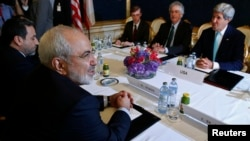 Iran's Foreign Minister Mohammad Javad Zarif (L) meets with U.S. Secretary of State John Kerry (R) at talks between the foreign ministers of the six powers negotiating with Tehran on its nuclear program in Vienna, July 13, 2014. REUTERS/Jim Bourg (AUS