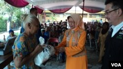 Ibunda Presiden Joko Widodo, Sujiatmi (tengah), menyerahkan paket sembako untuk warga di Solo. (VOA/Yudha Satriawan)