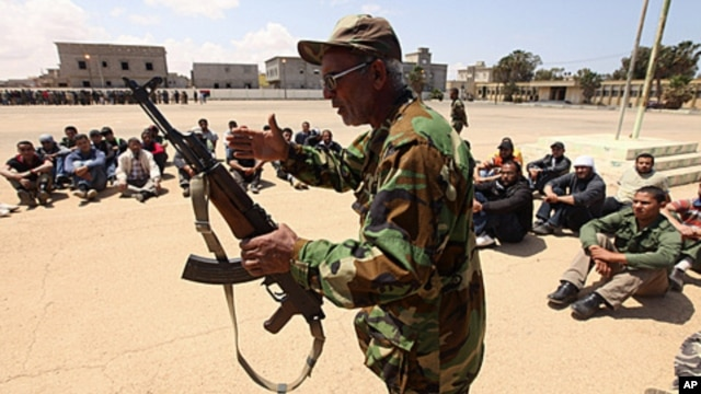 A rebel army officer teaches the use of a weapon to civilians, who have volunteered to join the rebel army, in Benghazi, May 11, 2011