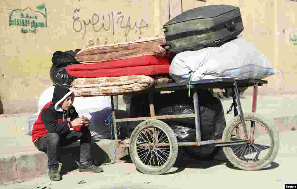 A boy sits next to a trolley containing belongings at the Karaj al-Hajez crossing, Aleppo, Feb. 9, 2014.