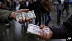 Iranian street money exchangers show currencies at Tehran's old main bazaar, Iran, Nov. 25, 2014.
