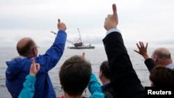 Viên chức bầu cử và Giám đốc điều hành Deepwater Wind chúc mừng trong buổi lễ đánh dấu việc lắp đặt công trình giá đỡ đầu tiên cho một trại điện gió ở vùng biển Đại Tây Dương ngoài khơi đảo Block, Rhode Island, hôm 27/7/2015.