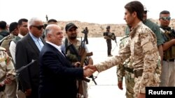 Iraqi Prime Minister Haidar al-Abadi, left, who was touring Anbar province, visiting army units, shakes hands with a Sunni tribesman at Camp Habbaniyah, in the eastern city of Ramadi, Iraq, April 8, 2015.