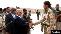 Iraqi Prime Minister Haidar al-Abadi, left, who was touring Anbar province, visiting army units, shakes hands with a Sunni tribesman at Camp Habbaniyah, in the eastern city of Ramadi, April 8, 2015.
