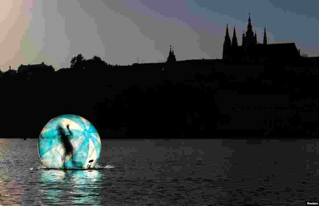 بازی دختربچه درون یک توپ بزرگ پلاستیکی در رودخانه واتاوا در پراگ
