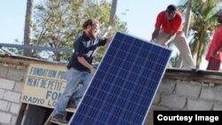 Christopher Alagna, Oficial de Tecnologías de la Información del PMA, ayuda a colocar paneles solares en una estación de radio en Nippes. Foto: WFP.