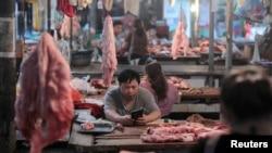 중국 허커우 야오족 자치현의 한 시장에서 상인들이 돼지고기를 팔고 있다.