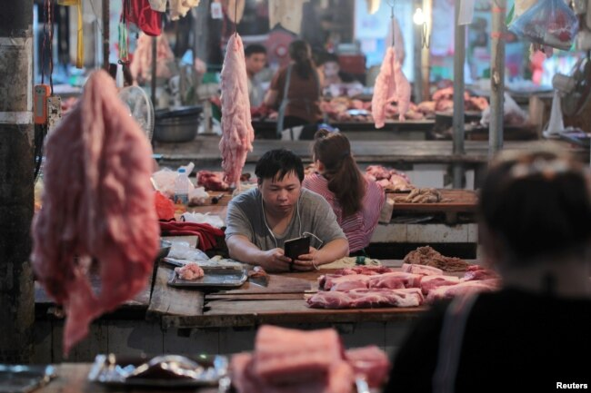 FILE - Vendors at their pork stalls at a market in Hekou Yao Autonomous County, Yunnan province, China, May 3, 2019.