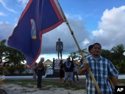 A man holds Guam flag during a peace rally in Hagatna, Guam, Aug, 14, 2017. The threatened missile attack by North Korea on Guam has prompted calls for peace from the island's indigenous people.