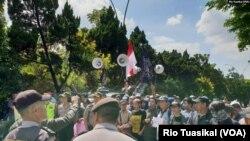 Sekelompok orang berunjuk rasa menolak diskusi buku Ahmadiyah di Bandung, Januari 2019, dengan pengawalan ketat kepolisian. (Foto: VOA/Rio Tuasikal)