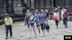 A tour guide leads a group of tourists in Siem Reap's Angkor Wat Temple on Saturday, July 16, 2016. (Photo: Leng Len/VOA Khmer)