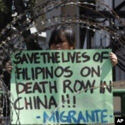 A member of Migrante International, a Filipino migrant organisation, displays a placard demanding legal assistance for her relatives during a protest outside the presidential palace in Manila, February 21, 2011.