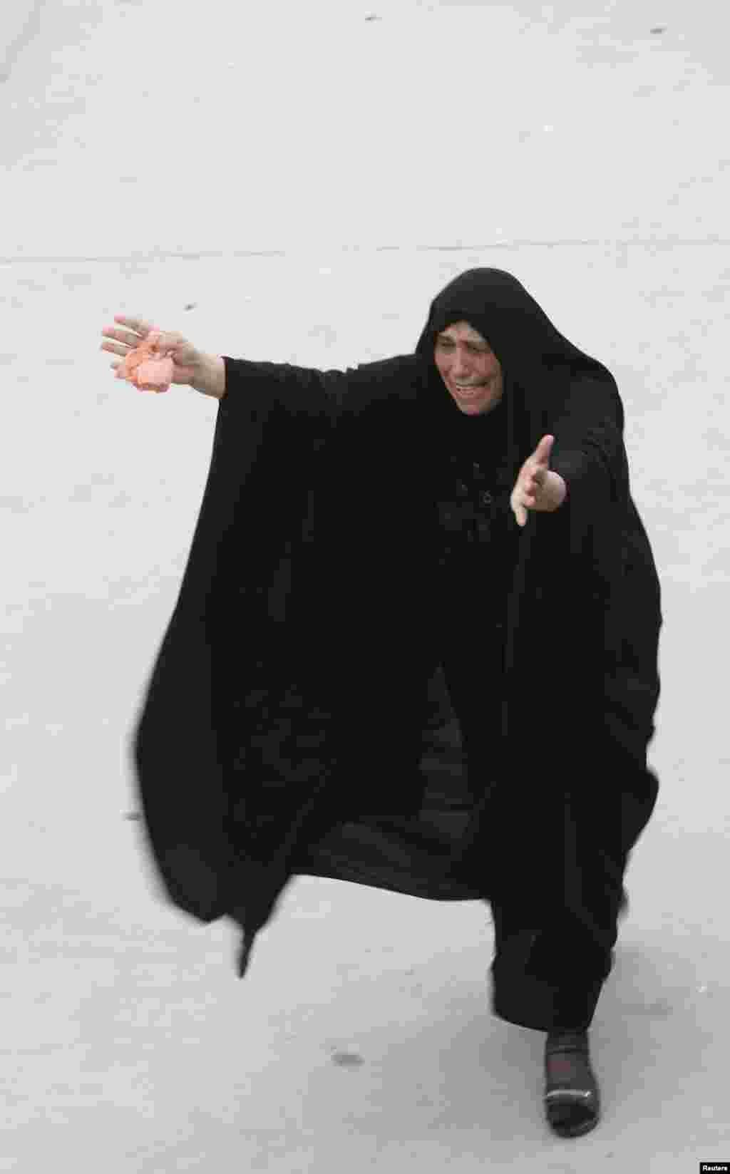 زنی در مراسم ختم يکی از قربانيان انفجار در حله (۹۰کيلومتری جنوب بغداد) عزاداری می کند. - ۱۸ اسفندماه