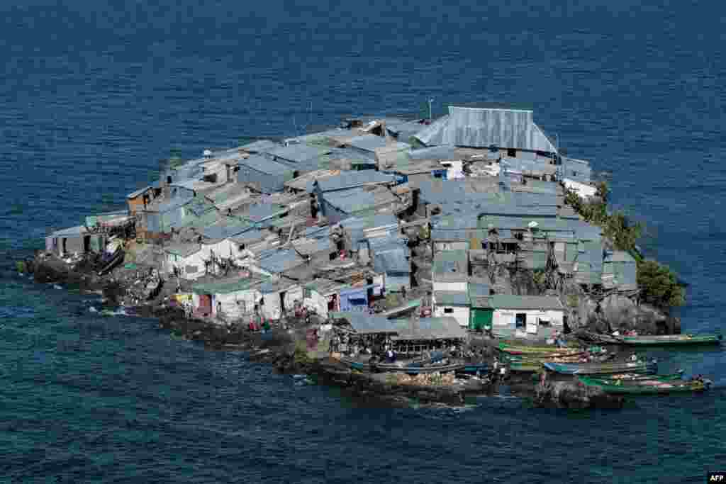 A rocky outcrop covered in metallic shacks, Migingo Island rises out of the waters of Lake Victoria on the border of Uganda and Kenya. The densely-populated island is barely a quarter of a hectare large, its residents crammed into a hodgepodge of corrugated-iron homes, bars, brothels and a tiny port.