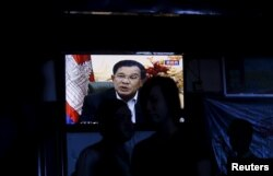 FILE - Cambodia's Prime Minister Hun Sen is seen on a television as he delivers a speech, at a restaurant in central Phnom Penh, Oct. 28, 2015.