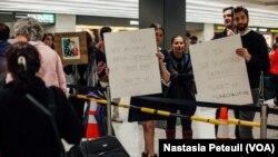 Des avocats accueillent les touristes et les résidents à l'aéroport international de Washington DC, le 31 janvier 2017. (VOA/Nastasia Peteuil)