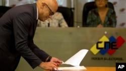 El ministro de Comunicaciones, Jorge Rodríguez, firma en nombre del gobierno un acuerdo para postergar las elecciones.