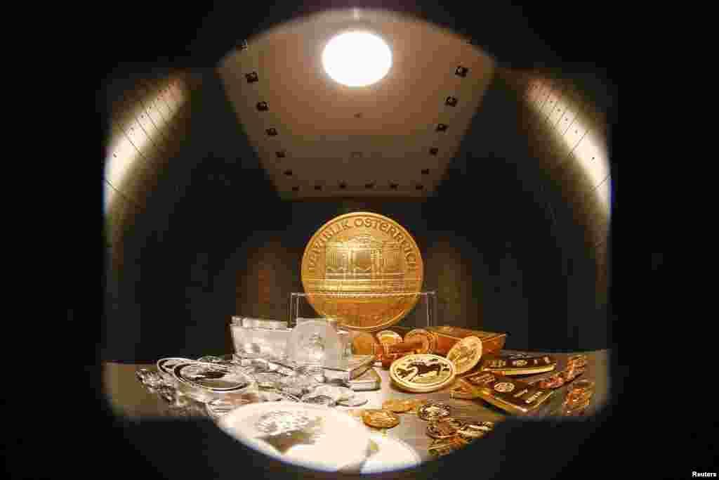 Batangan dan koin emas dan perak ditumpuk di sebuah meja di kota penyimpanan di rumah emas ProAurum di Munich, Jerman. Ancaman perang antara Ukraina dan Rusia membuat para investor menyelamatkan aset mereka hari Senin.