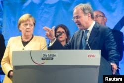FILE - Christian Democratic Union (CDU) leader and top candidate for chancellor Armin Laschet speaks next to German Chancellor Angela Merkel during his election rally in Stralsund, Germany, Sept. 21, 2021.