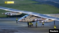Crew members push the solar-powered plane Solar Impulse 2 to its parking position at Nagoya airport after changing weather conditions thwarted a planned takeoff, June 24, 2015.