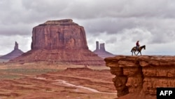A Navajo man on a horse poses for tourists in front of the Merrick Butte in Monument Valley Navajo Tribal Park, Utah, in May 2015. (AFP PHOTO/MLADEN ANTONOV)