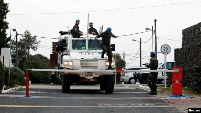 Armored car drives through gate of U.N. base near Quneitra border crossing between Israel and Syria, Israeli-occupied Golan Heights, March 8, 2013.