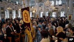 Foto yang diambil pada Minggu 15 April 2012, pemeluk Kristen Ortodoks Suriah menghadiri misa Paskah di Damaskus, Suriah. Umat Kristen yang berjumlah 10 persen dari populasi Suriah yang berjumlah lebih dari 22 juta, mengatakan mereka rentan terhadap kekerasan yang melanda negara terse but sejak Maret 2011. Mereka takut Suriah akan menjadi seperti Irak, di mana umat Kristen terjebak dalam peperangan antara kelompok-kelompok Islam. (AP Photo/Bassem Tellawi, File)