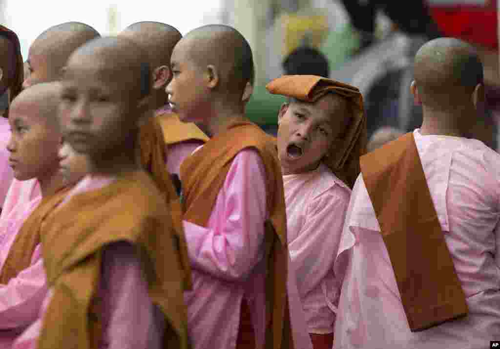 Novice Buddhist nuns line up after walking the streets to collect alms in central Yangon. Myanmar was trapped in a post-election limbo Tuesday with official results barely trickling in, although opposition leader Aung San Suu Kyi's party claimed a massive victory.
