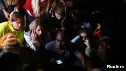 People listen to a radio as South African President Jacob Zuma announces the death of former South African President Nelson Mandela in Houghton, Dec. 5, 2013.