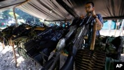 FILE - Weapons belonging to rebels of the Revolutionary Armed Forces of Colombia (FARC) are stored at a rebel camp in La Carmelita near Puerto Asis in Colombia's southwestern state of Putumayo.