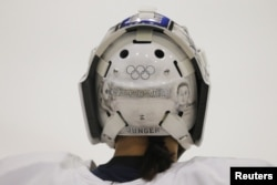 FILE - South Korean women's ice hockey goaltender So Jung Shin has the Olympic rings painted on her helmet, ahead of the South Korea Winter Olympics, during practice in Hamden, Conn., Dec. 27, 2017.